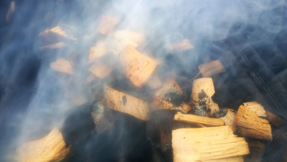 wood chips smoking on a gas grill