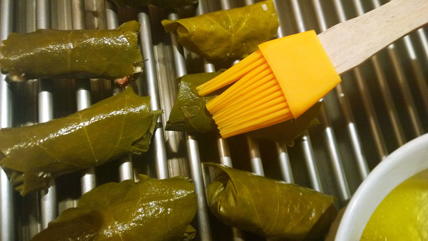 Basting grape leaves on grill